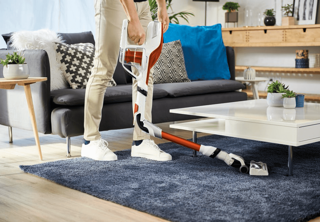 Man vacuuming under a white table